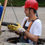 Mann mit rotem Helm und Arbeitskleidung steht in Abwasserschacht