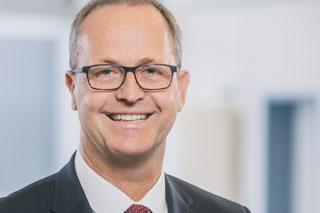 Portrait eines Manns mit Brille, Anzug und Krawatte
