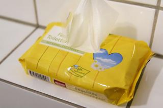 gelbe Packung Feuchttücher auf weißen Fliesen