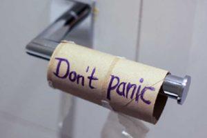 """Leere Klopapierrolle auf Metallhalter mit Aufschrift """"Don't panic"""""""